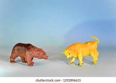 Miniature Toy Bear and Bull on Blue Background