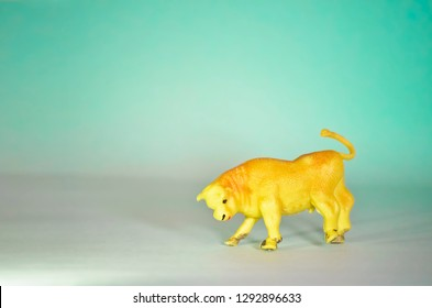 Miniature Toy Bull on Green Background