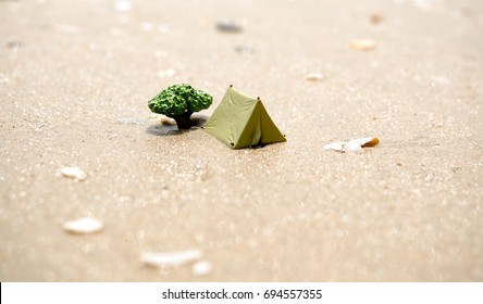 Miniature toy camping tent and tree on the sand beach.