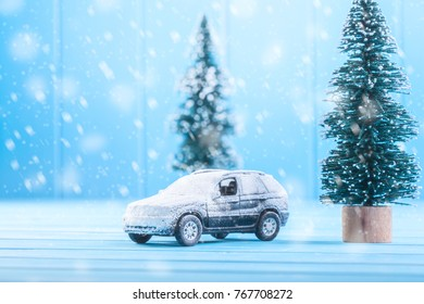 Miniature toy car with a Christmas tree on a wooden table. Imitation realistic scene.
