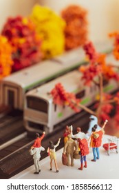 Miniature toy figurines of a group passangers waiting or waving at a train at a platform in autumn or fall season concept -  warm tone filter applied.