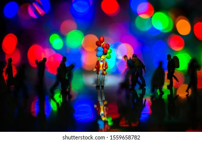 Miniature toy - a man holds colorful balloons among busy commuters crowd with colorful bokeh lights, waiting for someone concept.