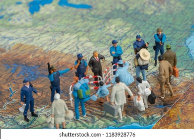Miniature toy people concept US border patrols against a group of migrant from Mexico