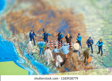 Miniature toy people concept US border patrols against a group of migrant from Mexico-Illustrative editorial