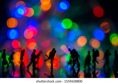 Miniature toy - Silhouette of a couple hugging together among busy commuters crowd with colorful bokeh lights, happiness concept.