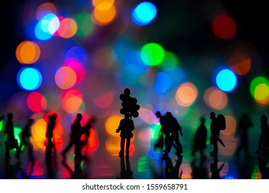 Miniature toy - Silhouette of a man holds colorful balloons among busy commuters crowd with colorful bokeh lights, waiting for someone concept.