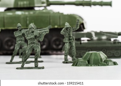 Miniature toy soldiers and tank, isolated on white background.