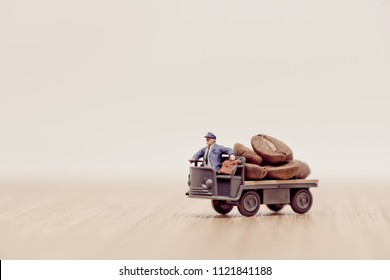 Miniature toy truck loaded with brown coffee beans.