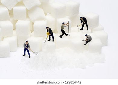 Miniature toy worker work with sugar