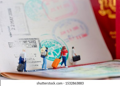 Miniature toys concept studio set up - a couple arrives or departs at an airport with the lady is talking to her mobile phone with visa passport stamps as the background.