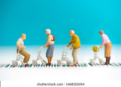 Miniature toys a group of old people with wheel chair crossing a road - road safety concept for senor citizen.