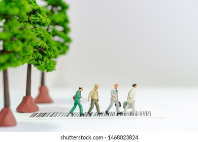 Miniature toys a group of people crossing a road with tree toys on the sidewalk - road safety concept.