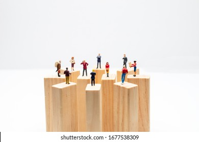 Miniature toys standing on wooden block - social distancing, anti-social or team work concept.