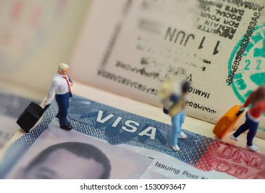 Miniature toys studio set up - expatriate business man and other travellers travel with visa on passport as background.