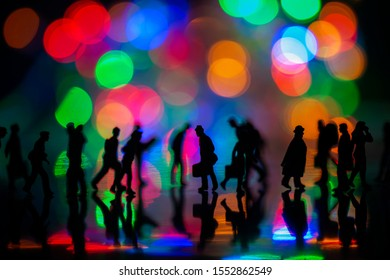 Miniature toys studio set up - Silhouette side view of people busy walking with colorful blurred bokeh background. Focus at the man in the middle with briefcase and a hat - a lost man in the city.