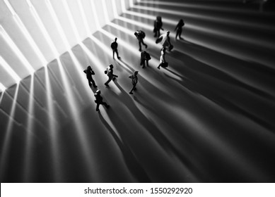 Miniature toys studio set up - Top view of black and white effect of people with long shadows busy walking during sunrise or sunset. Noise added for dramatic effect.
