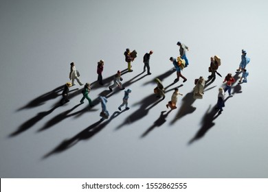 Miniature toys studio set up - Top view of people with long shadows busy walking during sunrise or sunset. Focus at the sad business man with hands behind his back.
