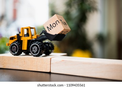 Miniature tracktor lift up Monday wooden block using as business and industry concept