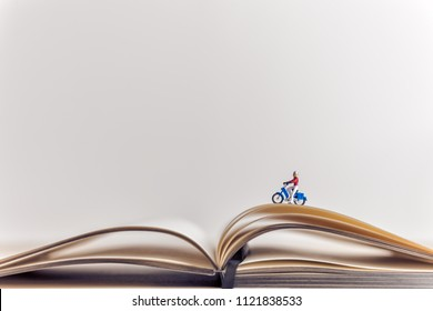 Miniature traveler riding a motorbike over opened book. Travel concept
