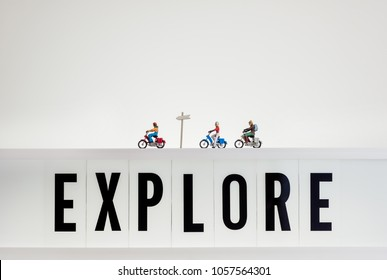Miniature travellers ride over lightbox with the word Explore.