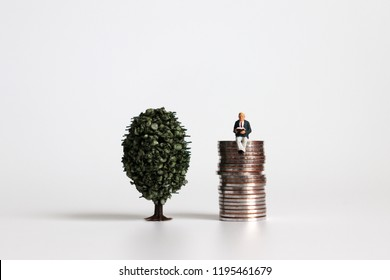 A miniature tree next to a miniature man sitting on a pile of coins.