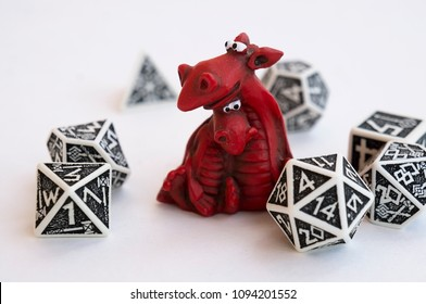 Miniature of two cute red dragons and black and white dices for rpg, board or tabletop games