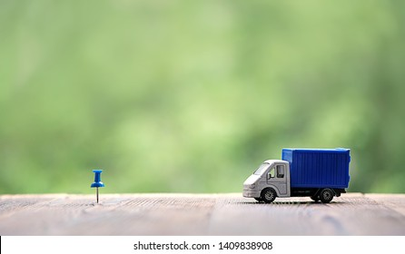 miniature van on wood background. truck toy and destination point indicated by blue pushpin. Concept for visualization of delivery services, logistics, business, forwarding, travel, cargo delivery.
