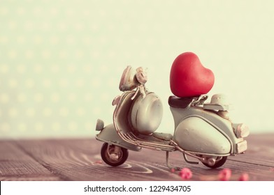 Miniature vintage blue motorcycle carrying tiny red heart in nursery room