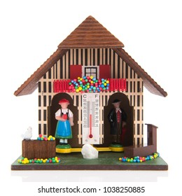 Miniature weather house with man and woman indoor and outdoor