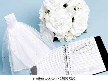 A miniature wedding dress and white bouquet of roses, with a day planner marked Wedding.