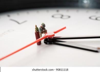 Miniature Welder At Work. A miniature figurine of a welder kneels alongside his acetylelne tanks