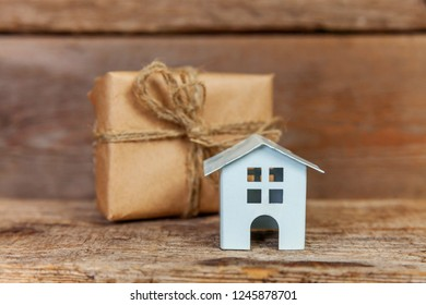 Miniature white toy house and gift box wrapped craft paper on old shabby rustic wooden background. Mortgage property insurance dream home concept. Buying new house for family