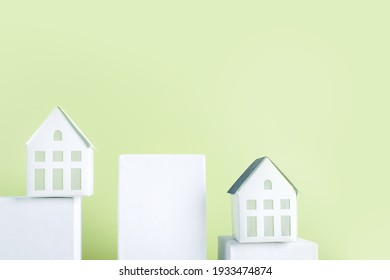 Miniature white toy house on podiums with color green pastel background. Mortgage property insurance home concept