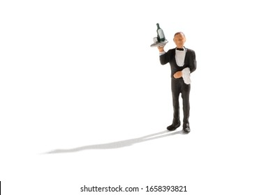 Miniature wine waiter with bottle of wine on tray in a tuxedo at a nightclub or hotel over a white background