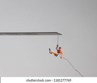 A miniature woman hanging by a rope at the edge of a cliff.