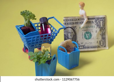 Miniature woman with her shopping purchases in a cart. Huge savings or spending concept. Thrifty mom saves on her bill at the store by getting a good deal. Woman shops the sales and makes budget.