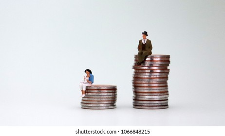 A miniature woman holding a baby on a pile of coins. The concept of analyzing the causes of the wage gap between men and women.