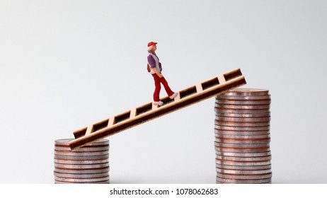 A miniature woman walking from one pile of low coins to another. The concept of income gap.