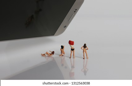 Miniature women changing clothes. The concept of illegal filming offences.