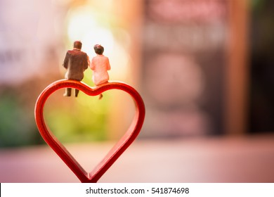 Miniature of a women and a man in love sitting on heart sign bench with bokeh light copyspace, couple in love and pre-wedding background concept