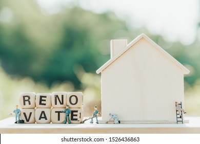 Miniature of wood block with word renovate. Figure of wood home and people of technical. Property construction concept