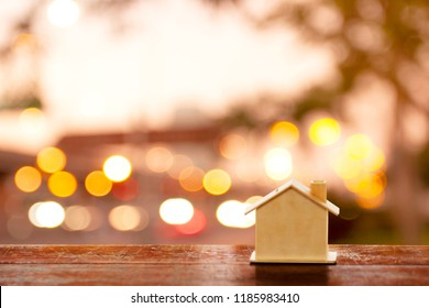 miniature wood house on wooden mock up over blurred sunset and lighting bokeh background.Image for property real estate investment concept.