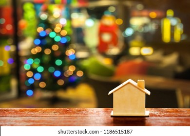 miniature wood house on wooden mock up over blurred Christmas decoration background.Image for property real estate investment concept.
