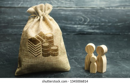 Miniature wooden family figurines stand near a money bag. The concept of savings. Budget planning. Distribution of profits. Financial management. Accumulation of funds. Family income