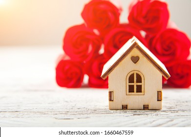 Miniature wooden house on a background of roses and copy space. Sale, purchase, rental of apartments in the spring. Spring gift concept.