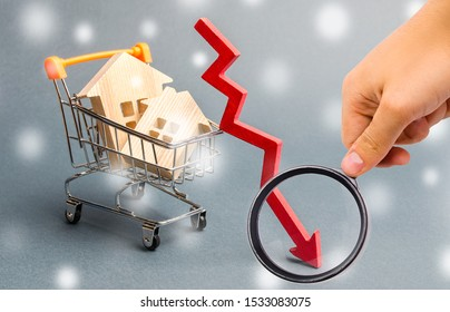 Miniature wooden houses in the supermarket trolley and down arrow. The concept of low housing demand. Discounts for real estate in the winter. Mortgage interest rates. Cheap cost. Christmas Snowflakes