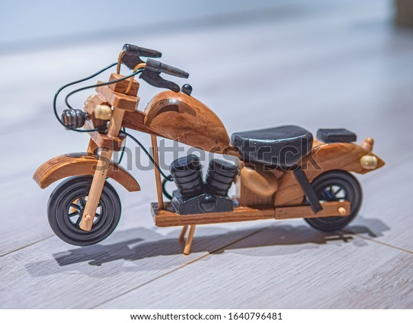 Miniature wooden motorcycle isolated on a wooden surface. Perfect gift for kids or motorbike lovers.
