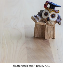 A miniature wooden owl dressed as a professor with a graduation hat. Read a book on the background of a brown wooden table. A small gift for a degree.