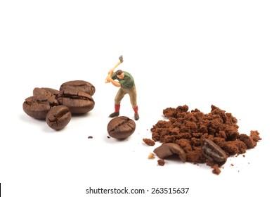 Miniature worker with axe working on a coffee bean on white background