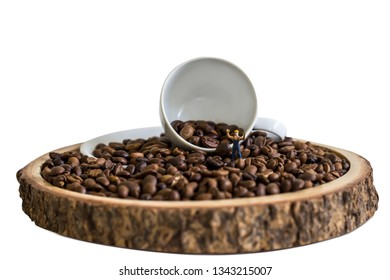 miniature worker and coffee bean with white cup on wooden plate over blurred plantation of coffee tree with sun lighting.